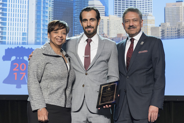 Photo of three people standing with the middle holding an award. Caption: Lisa Washington (left) executive director and CEO of the Design-Build Institute of America, and the organization's chairman Praful Kulkarni (right), presented Fulton Schools faculty member Mounir El Asmar the Distinguished Leadership Award at the DBIA annual national conference.Photograph courtesy of Design-Build Institute of America.