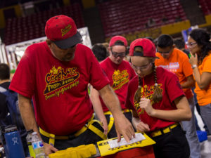 A mentor works with a student team member at the FIRST Robotics Competition Arizona State Championship at Wells Fargo Arena.