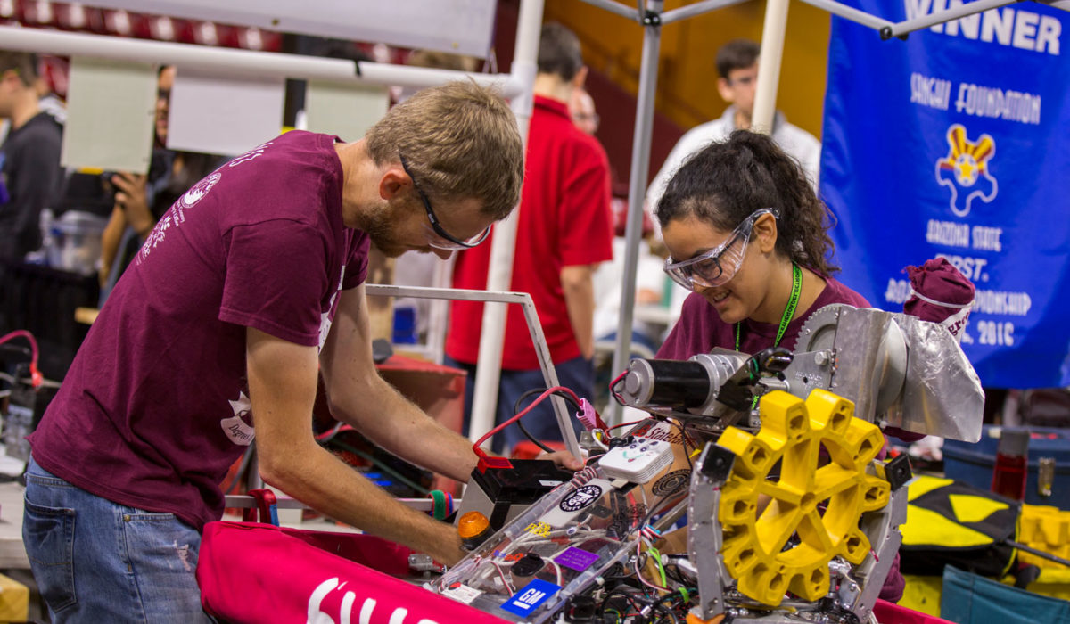 """Students work on their robot and a """"Winner"""" banner is in the background at the FIRST Robotics Competition Arizona State Championship at Wells Fargo Arena."""