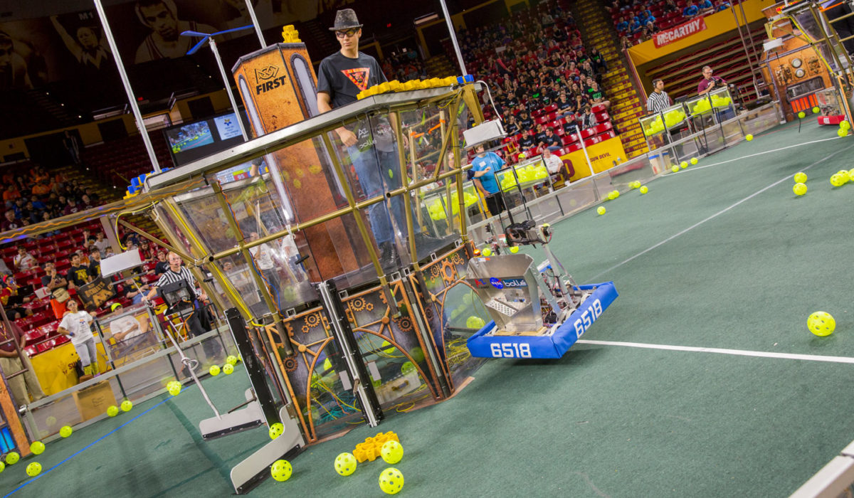 A student stands in a tower as part of the competition at the FIRST Robotics Competition Arizona State Championship at Wells Fargo Arena.