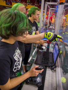 Three students control their robots at the FIRST Robotics Competition Arizona State Championship at Wells Fargo Arena.