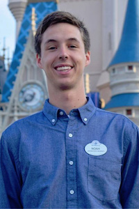 Portrait of Noah Livingston in front of a Disney castle