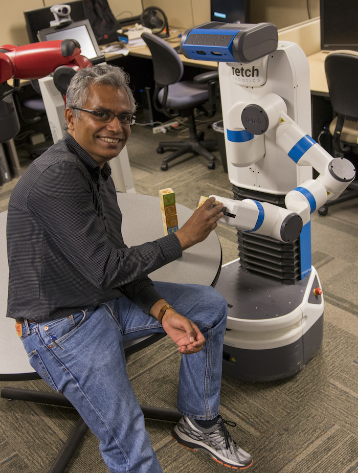 Photo of Subbarao Kamphampati with robot. Caption: Professor Subbarao Kamphampati is president of the Association for the Advancement of Artificial Intelligence. His research in that area focuses on automated planning, machine learning, robotics and design of human-aware artificial intelligence systems. Photographer: Marco-Alexis Chaira/ASU