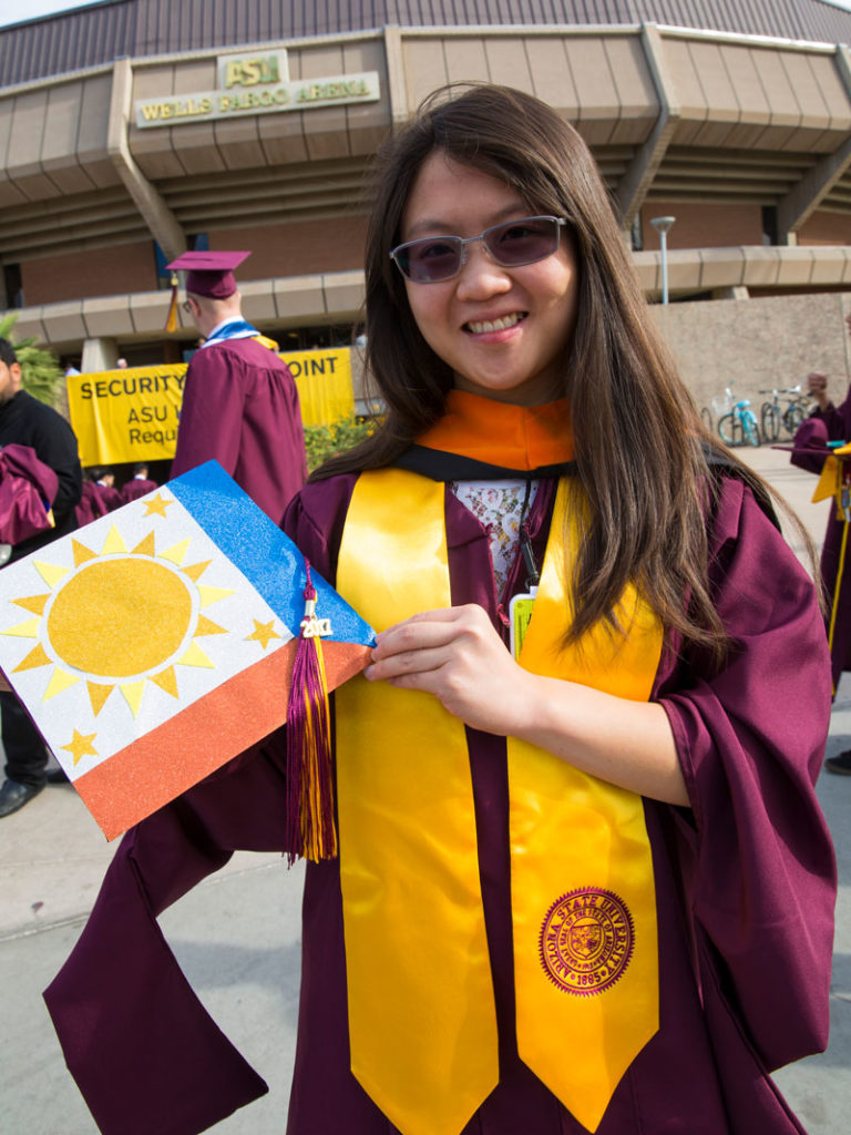 Brigitte Lim shows off her mortarboard with a solar-themed design in front of Wells Fargo Arena at the Fulton Schools Convocation ceremony.