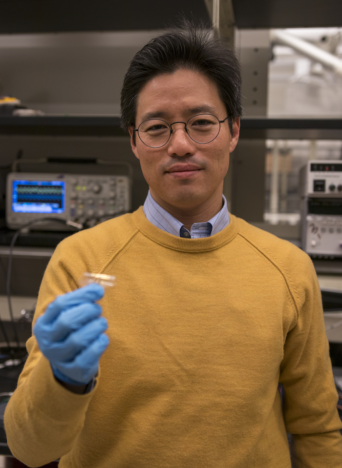 Portrait of Junseok Chae holding a device. Caption: Junseok Chae holds a prototype of the wireless, fully passive multi-channel neural recorder his team is developing. Photographer: Marco-Alexis Chaira/ASU