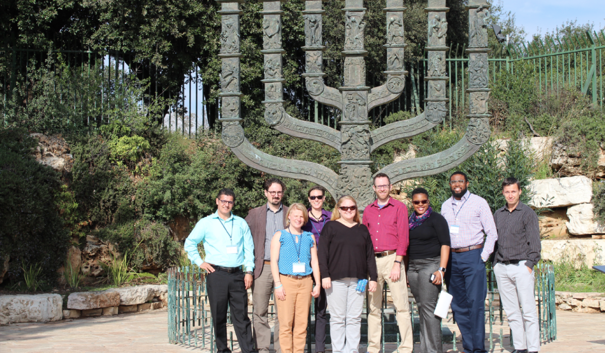 Group of people standing in front of large Menorah sculpture. Caption: The group in front of a large Menorah sculpture near the Israeli Parliament building. Photograph courtesy of Jeremi London/ASU