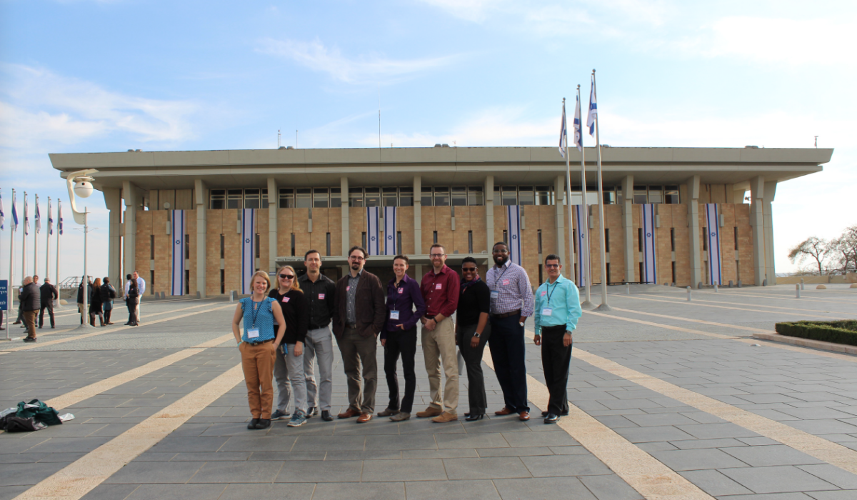 Photo of a group of people standing in front of a building. Caption: The ASU group poses outside the entrance to the Israeli Parliament building, called the Knesset, in Jerusalem. Photograph courtesy of Jeremi London/ASU