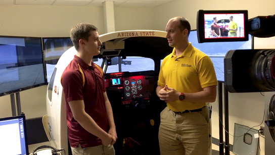 A student and faculty member talk on camera in front of a flight simulator. Caption: Senior Lecturer Benjamin Mertz (right) talks with a student on camera as part of the filming of an online lecture. The Fulton Schools are investing in facilities, tools and staff to enhance course materials for online engineering students. Photographer: Andrew Bautista/ASU