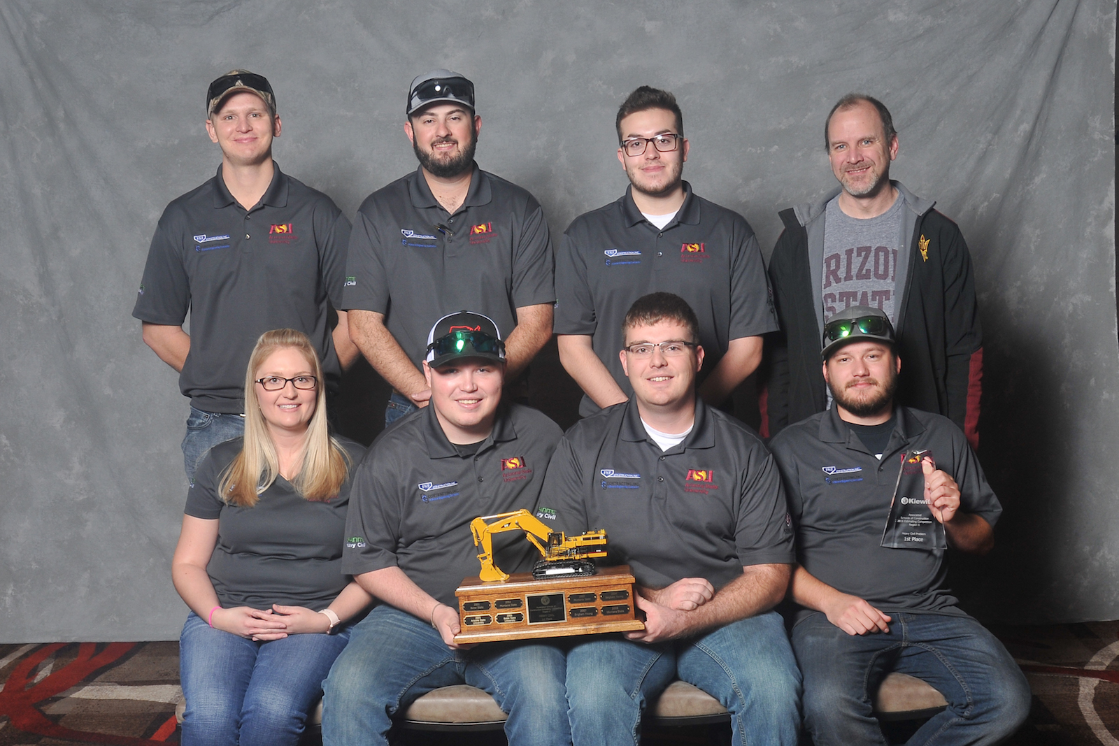 Photo of eight people posed holding a trophy. Caption: First-place heavy/civil team: (left to right, back to front) Jacob Dittbrenner, Samuel Schlinger, Nathan Eldodt, coach Aaron Cohen, Brittany Wells, Tanner Schafersman, Jacob Ellis and Shay Snider. Photo by Associated Schools of Construction for Regions 6 and 7
