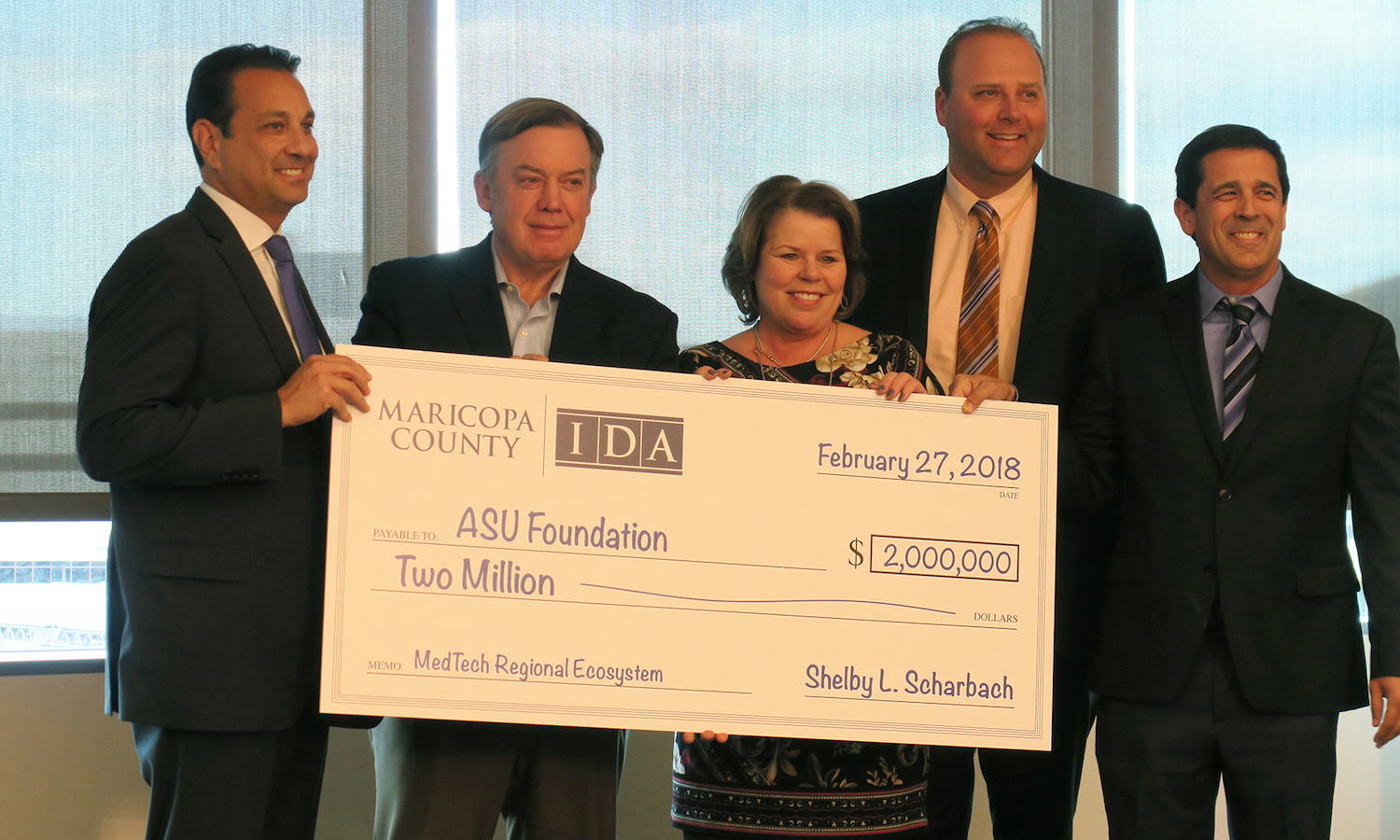 Photo of five people standing behind an oversized check. Caption: ASU President Michael Crow (second from left) accepts $2 million check to kick off a medical technology workforce development initiation. Pictured with Maricopa County Board of Supervisors Chairman Steve Chucri, District 2, MCIDA Executive Director Shelby L. Scharbach, MCIDA Board Member Jeremy Stawiecki, and MCIDA Business Development Officer Gregg Ghelfi. Photographer: Charrie Larkin/ASU.