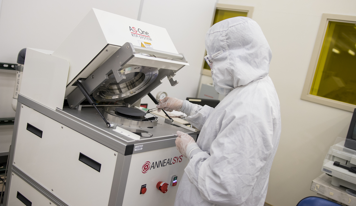 Photo of a student working in a clean room. Caption: A student is pictured at NanoFab unloading a wafer — a thin slice of semiconductor materials used to make electrical circuits — from the vacuum of a rapid thermal processing machine. It's one of the facility's advanced research tools that enable both established companies and startup ventures to perform state-of-the-art fabrication, prototyping and testing for new products. Photographer: Marco-Alexis Chaira/ASU