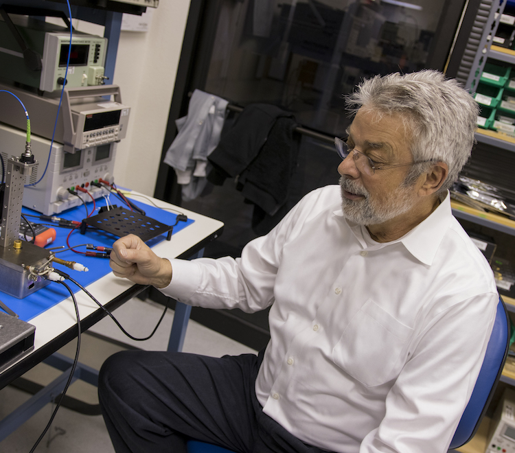 Photo of a man sitting next to equipment on a table. Caption: Laser Components DG general manager Dragan Grubisic came to NanoFab to do the groundwork that laid the technological foundation for the company about 15 years ago. Advancements achieved through an ongoing collaboration with the ASU facility has contributed to the company's steady growth. Photographer: Marco-Alexis Chaira/ASU