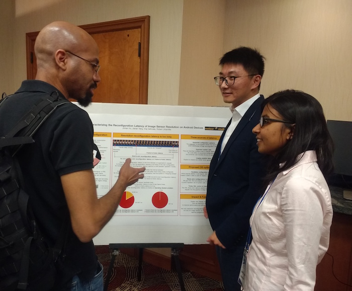 Photo of student presenting to two others in front of a poster. Caption: Computer engineering doctoral student Jinhan Hu (second from right) discusses his research on reducing mobile vision application power consumption with other researchers attending ACM HotMobile '18. Hu presented one of four demonstrations — his first public talk at a conference. Photo courtesy of Robert LiKamWa.