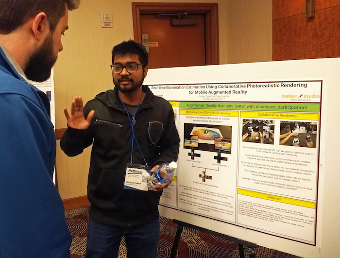 Photo of student presenting in front of poster. Caption: Computer science graduate student Siddhant Prakash presents his poster highlighting research on environmental sensing for mobile augmented reality applications to a fellow ACM HotMobile '18 attendee. Prakash won Best Poster out of 16 posters at the workshop. Photo courtesy of Robert LiKamWa.