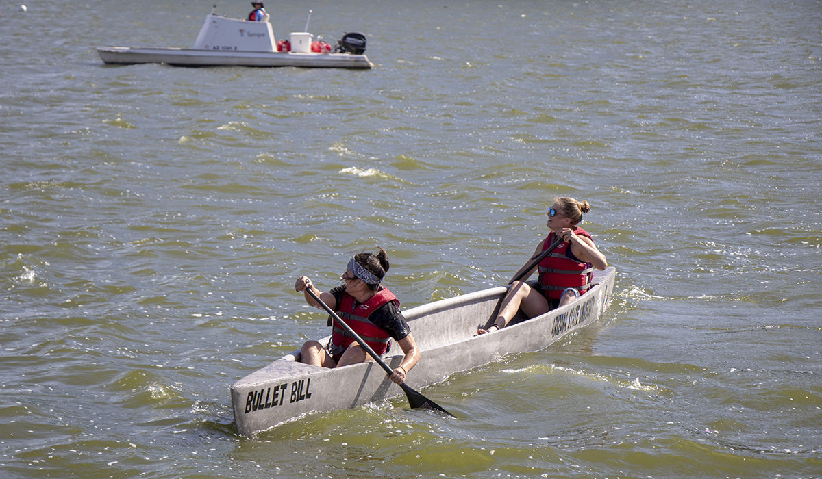 "Photo of two people in a canoe. Caption: Tempe Town Lake near the Arizona State University campus was the site of the concrete canoe contest, a signature event in the American Society of Civil Engineers annual student competition. Pictured are two ASU students steering their team's canoe, named ""Bullet Bill."" Photographer: Marco-Alexis Chaira/ASU"