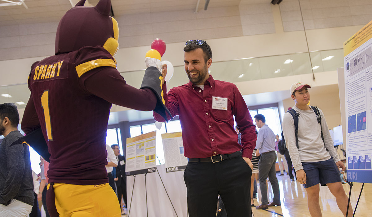 Photo of Sparky the Sun Devil giving a high five to a student. Caption: Cesar Tamayo explained to Sparky his research for an autonomous driving neural network algorithm that uses multiple cameras to help determine if a car is going to crash. Tamayo says he has learned so much about teamwork as part of his FURI research project, and has now submitted his second paper as an undergraduate student. Photographer: Marco-Alexis Chaira/ASU