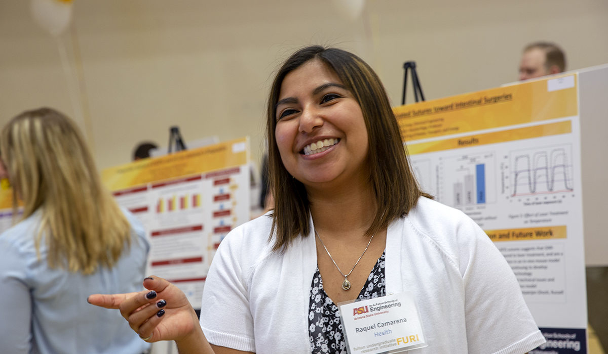 Photo of a girl smiling in front of a poster. Caption: Raquel Camarena, a graduate student in industrial engineering, explains her master's thesis project on improving the identification and treatment of Alzheimer's Disease at the FURI Symposium. The hands-on experience with operations research helped her land a full-time job with Raytheon after graduation. Photographer: Jessica Hochreiter/ASU