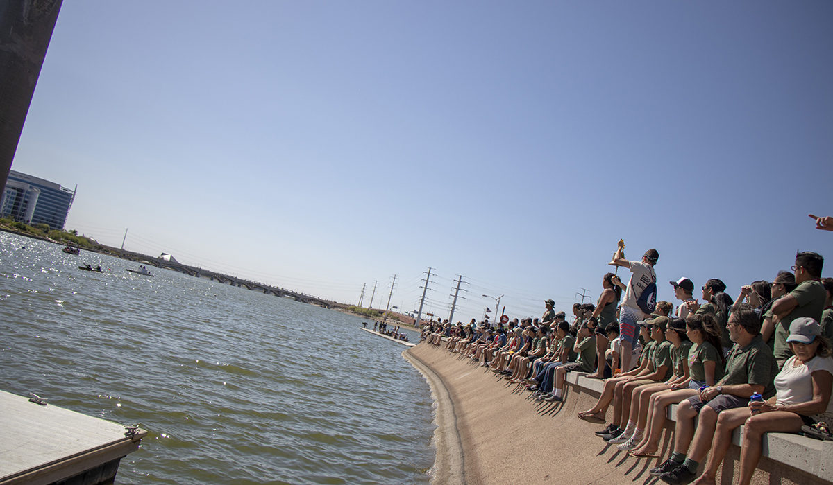 Photo of people sitting on the shore. Caption: Students from 18 universities, along with some of their family members, friends and alumni of their schools, gathered along the banks of Tempe Town Lake to cheer on students in the concrete canoe competition. Photographer: Marco-Alexis Chaira/ASU
