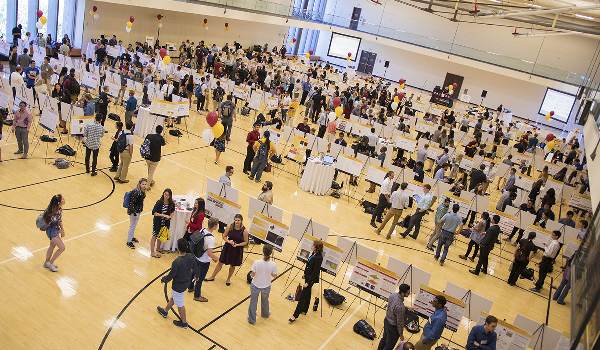 Overhead photo of posters in a gym. Caption: More than 200 student researchers presented their projects at the Spring 2018 FURI Symposium. Students conduct hands-on research in the labs of the Fulton Schools' world-renowned faculty to help solve real-world challenges in health, sustainability, energy, security and education. Photographer Marco-Alexis Chaira/ASU