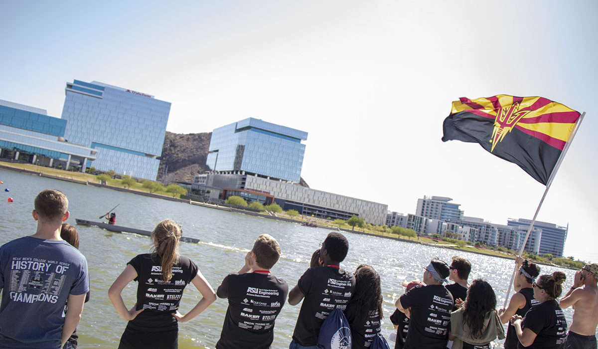 Photo of a group of people looking out onto the water. Caption: ASU students shouted encouragement and waved a university flag in support of the Ira A. Fulton Schools of Engineering students participating in the concrete canoe contests. Photographer: Marco-Alexis Chaira/ASU