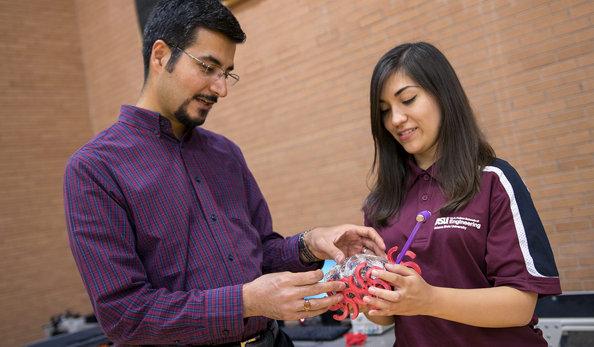 Photo of professor and student holding an object. Caption: Assistant Professor Hamidreza Marvi and mechanical engineering senior Hailey Burch examine a bio-inspired robot developed in Marvi's lab. Burch studied and optimized the robot's stride length and frequency in sandy environments — modeled after a basilisk lizard's movements — for use in search and rescue vehicles. Photographer: Marco-Alexis Chaira/ASU