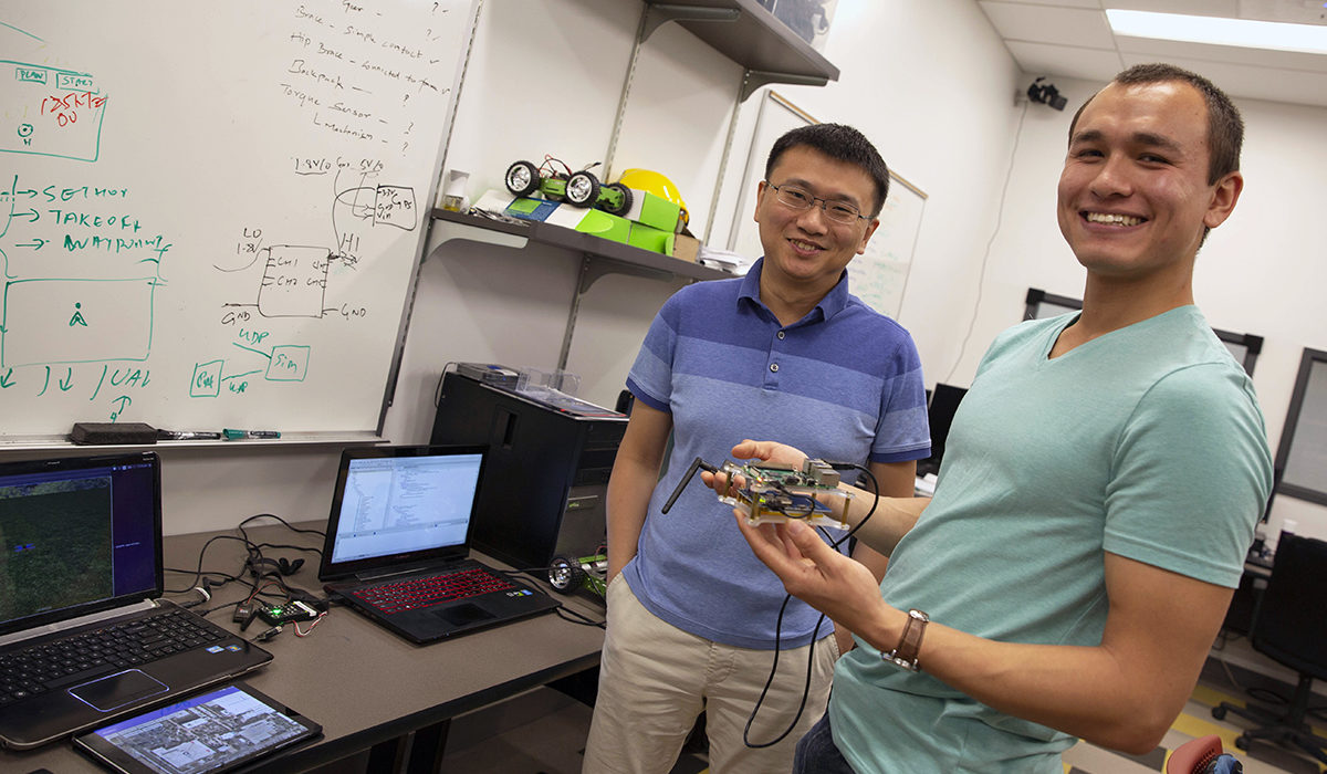 "Photo of professor and student standing. Caption: YiZhuang ""JJ"" Garrard (right) poses with his mentor, Assistant Professor Wenlong Zhang in the lab. Garrard's research focused on using low-cost and easy-to-use quadcopters for performing topological surveys. Garrard's research was funded by the Kern Family Foundation for his entrepreneurial approach to his project. Photographer: Jessica Hochreiter/ASU"