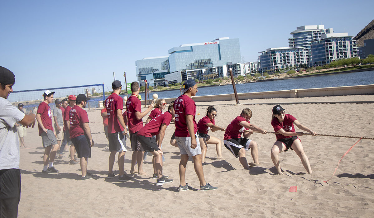 Photo of students playing tug-of-war. Caption: Students got a break from some of tension of their demanding technical competitions by participating in traditional contests of brute strength and tenacity like tug-of-war battles. Photographer: Marco-Alexis Chaira/ASU