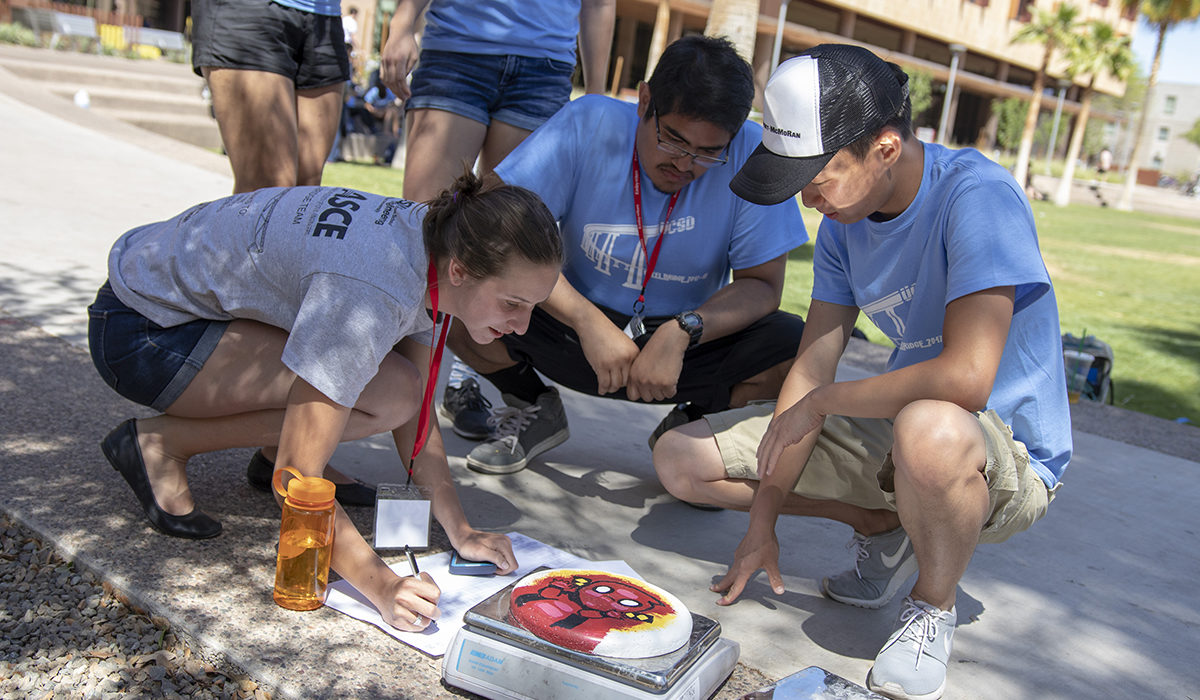 "Photo of students weighing a concrete frisbee. Caption: Students on a University of California, San Diego team weigh their concrete ""Frisbee"" disc to check if it matches specifications for entry into one of the ASCE competitions. Photographer: Marco-Alexis Chaira/ASU"