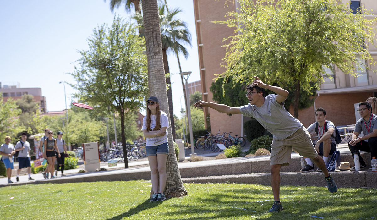 "Photo of a student throwing a concrete frisbee. Caption: A student displays the aerodynamic characteristics of a concrete disc in preparation for the ""Ultimate Frisbee"" contest. Photographer: Marco-Alexis Chaira/ASU"