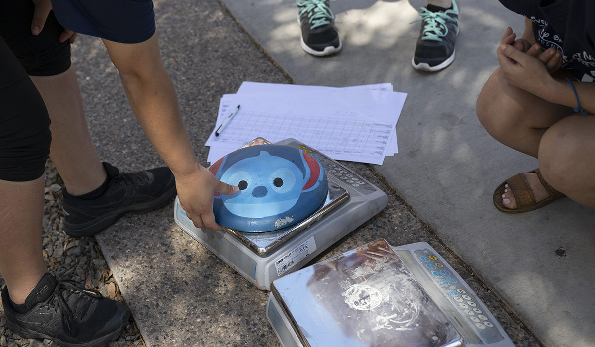 "Photo of a concrete frisbee being weighed. Caption: Students get creative and whimsical in naming, designing and decorating the objects they construct for various ASCE competitive events — like this concrete disc adorned by a student team from the University of Hawaii at Manoa with a visage of the cartoon character Stitch from the ""Lilo and Stitch"" animated science fiction children's movies. Photographer: Marco-Alexis Chaira/ASU"