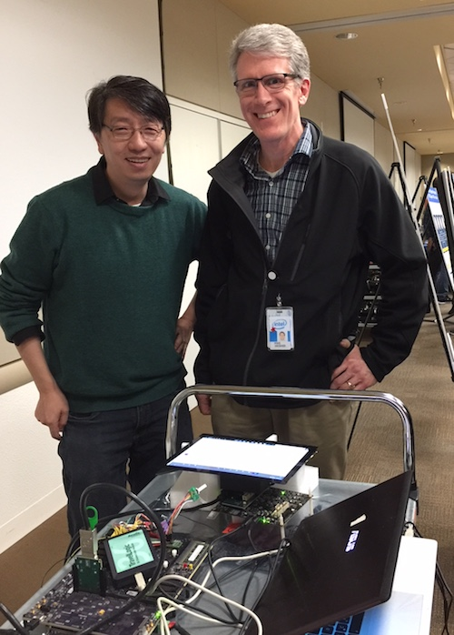 Photo of two men standing behind computer equipment. Caption: Intel engineers Kevin Zhu (left) and Michael Deisher pictured at an Intel internal computer architecture summit. Deisher has worked at Intel since earning his doctoral degree in electrical engineering from Arizona State University in 1996. Photographer: Gayle McCarthy/Intel