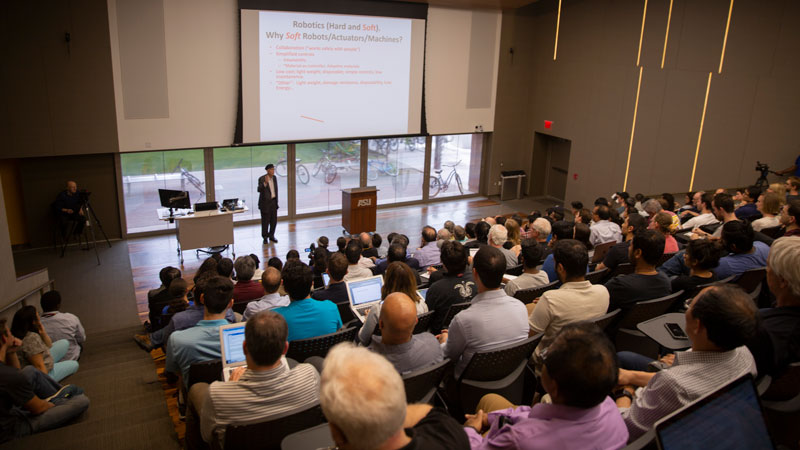 A man stands in the front of a room and addresses a crowd. Caption: George M. Whitesides spoke about soft robotics to a full auditorium at Arizona State University's Tempe campus on April 4.