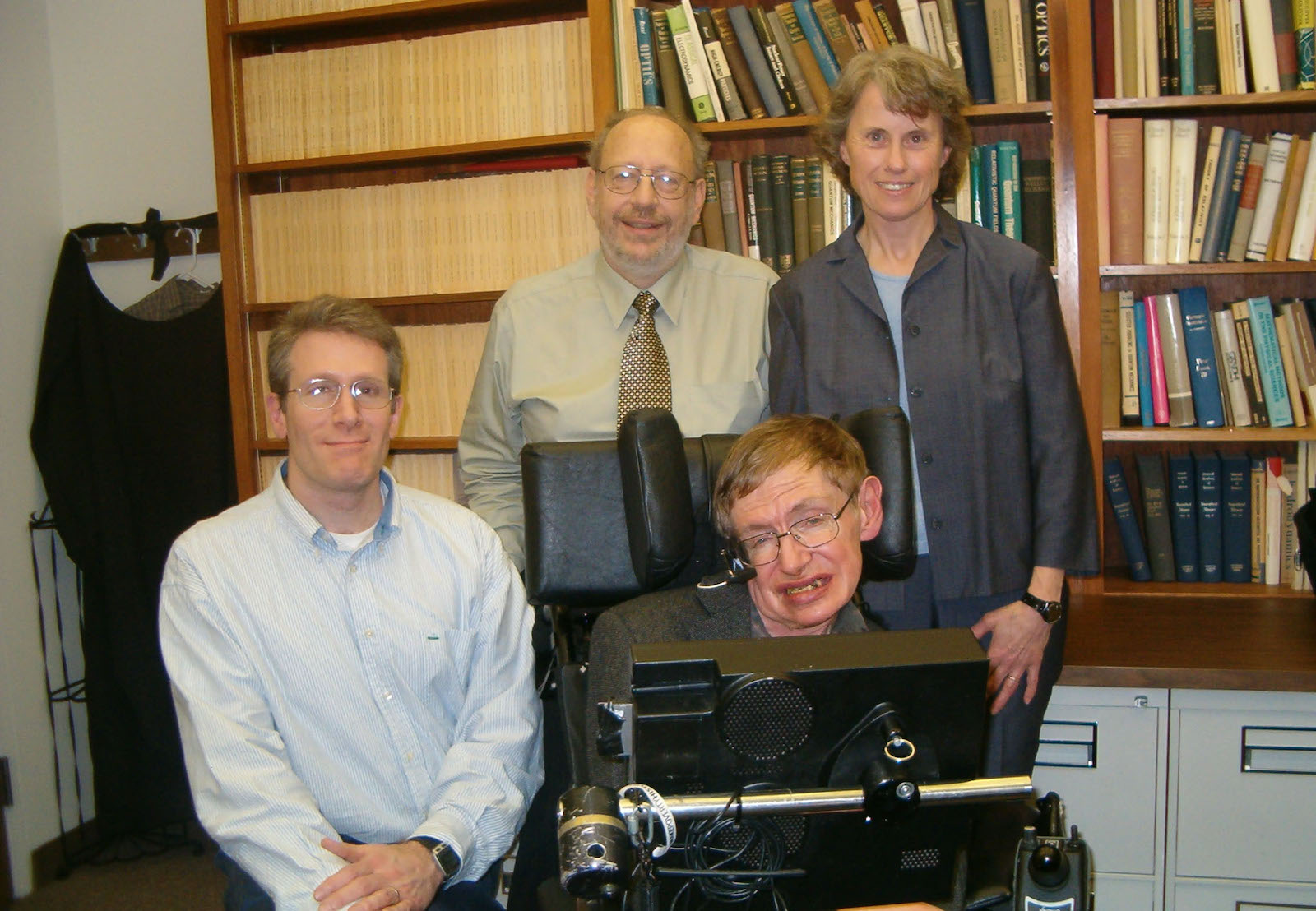 Photo of three people with Stephen Hawking. Caption: Famous physicist Stephen Hawking (foreground), disabled by neuromuscular disease, depended on scientists and engineers who developed the technologies that enabled him to overcome the loss of speech. Speech synthesis and acoustics experts who helped him included (from left behind Hawking) ASU alum Michael Deisher, the late Edward Brucket and Corine Bickley, pictured here in 2005.  Photograph courtesy of Michael Deisher.