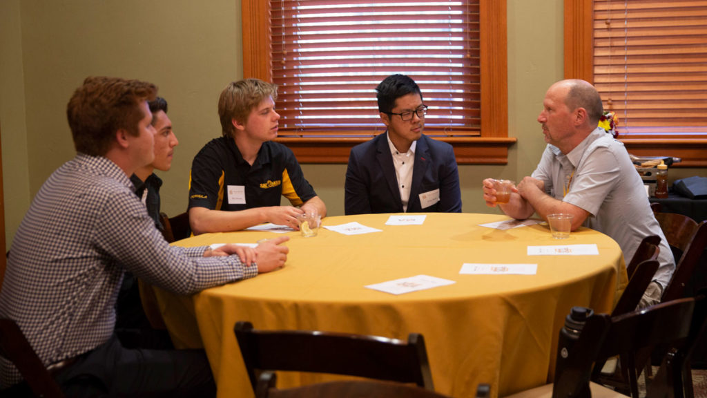 Five people talk at a table. Caption: Faculty Associate James Hartman (right) talks with John Baik (second from right), a software developer from CueSquared, and several materials science and engineering students at Industry Night.