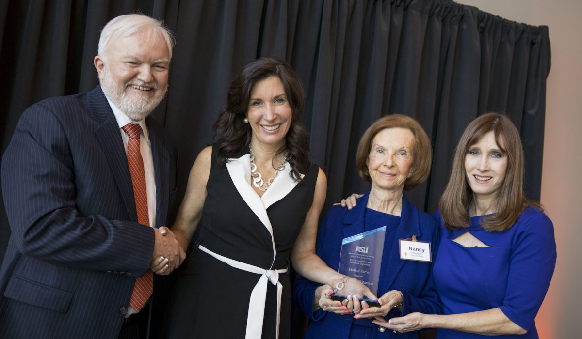 Photo of a man with three women holding a trophy