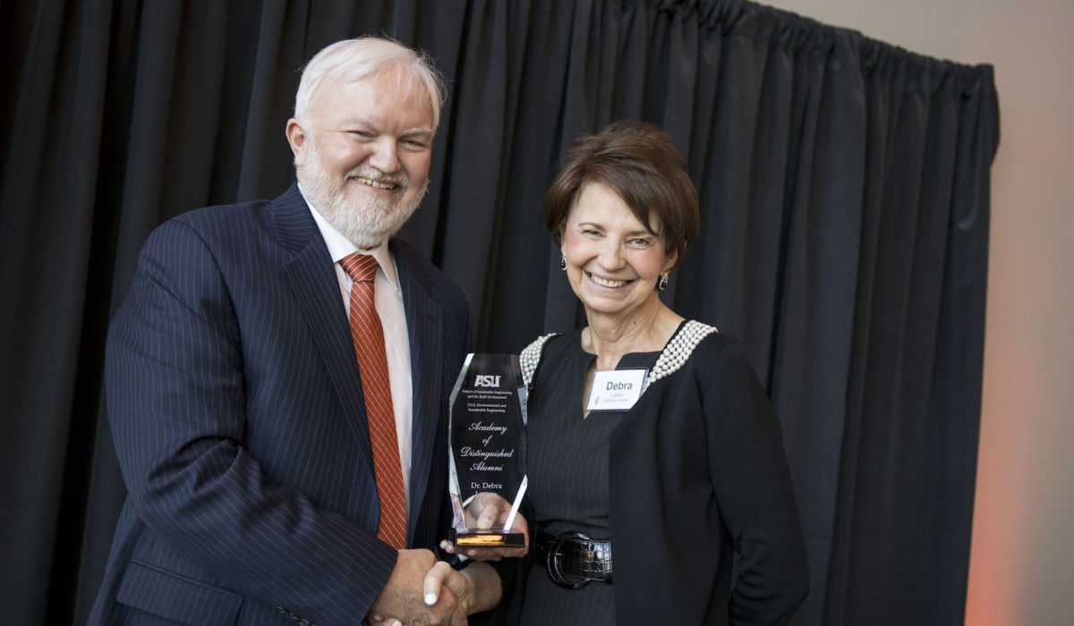 Photo of a man and a woman holding a trophy