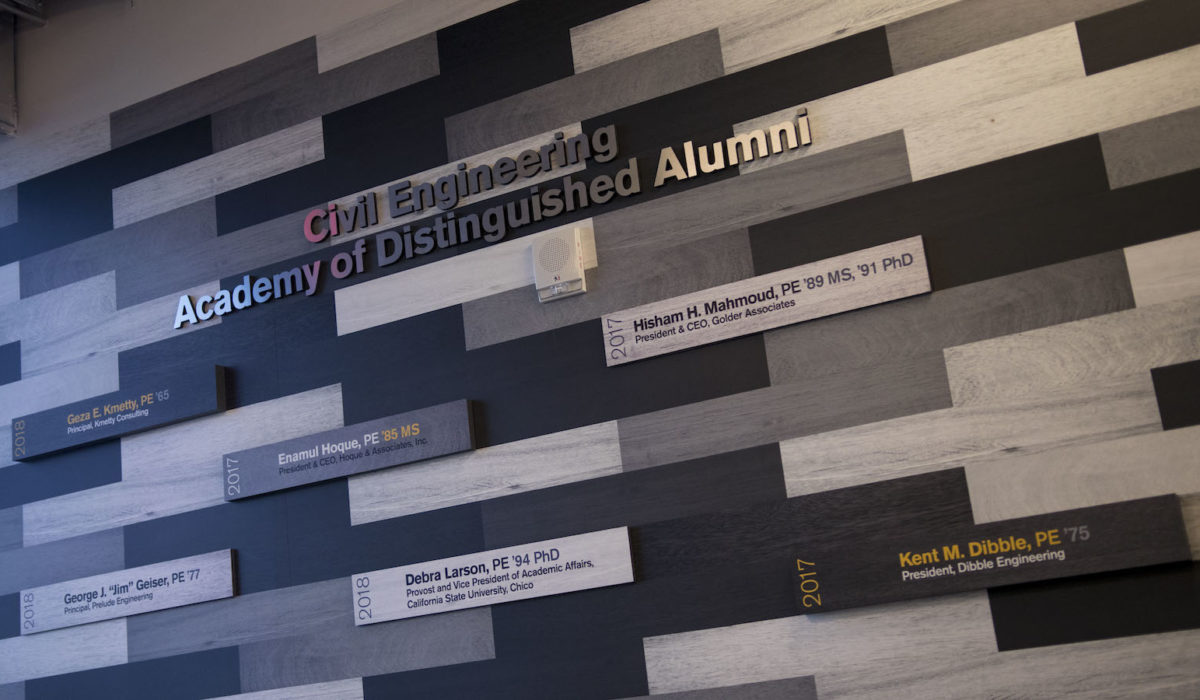 Photo of a wall with names and dates under a sign that says Academy of Distinguished Alumni