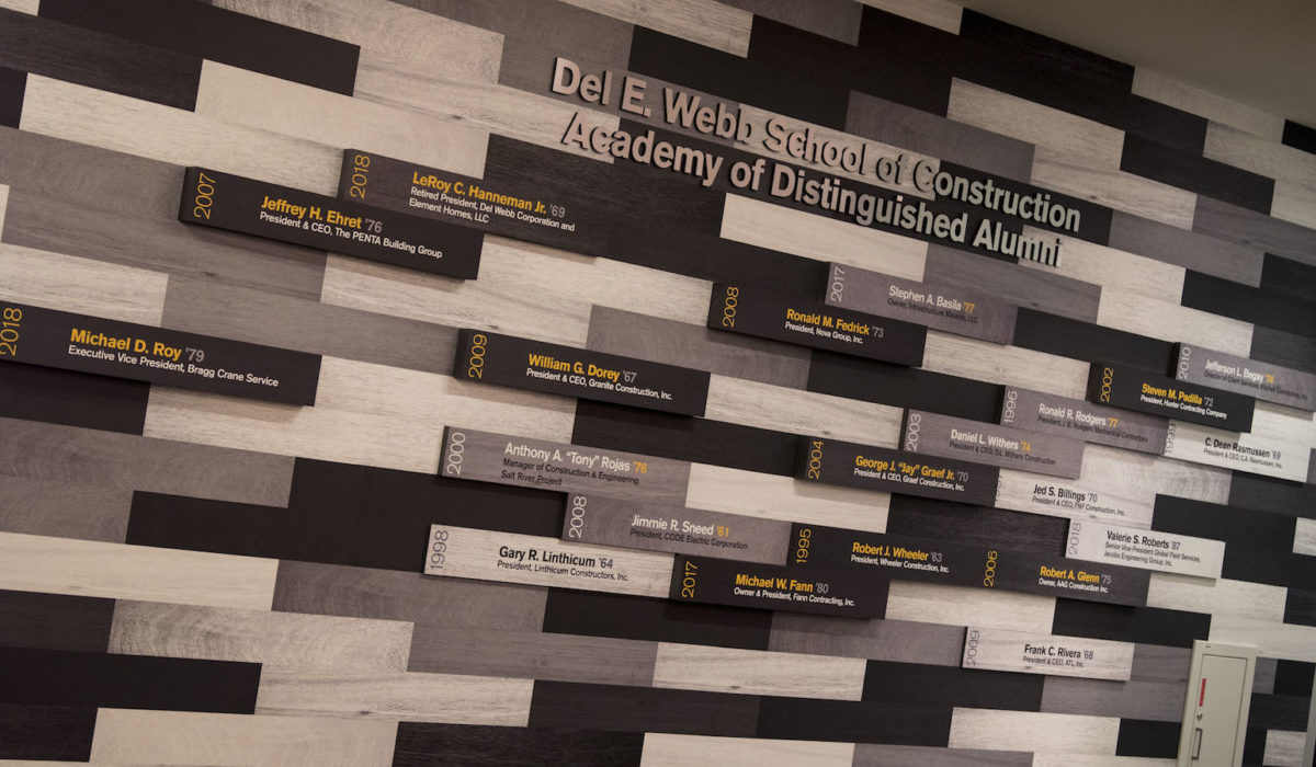 Photo of a wall with names and years under a sign that says Academy of Distinguished Alumni