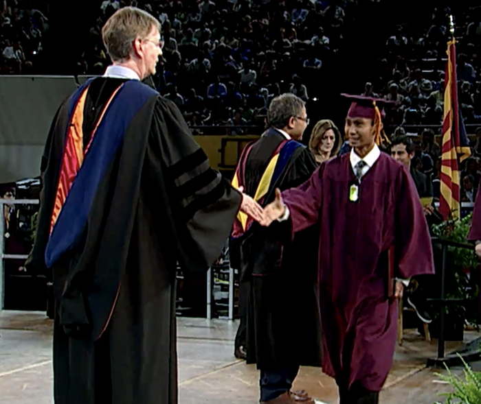 John Cava walking across the stage at convocation.