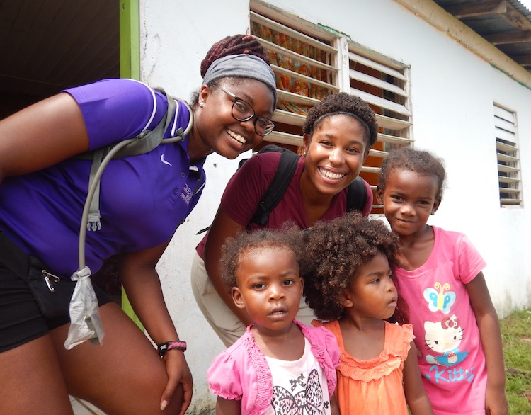 Photo of two women with three little girls. Caption: Shakira Hobbs and Evvan Morton is a picture with children in the Sittee River community as they conduct a house-to-house census in the village.  Morton and Hobbs also interviewed residents about their waste disposal practices as part of their efforts to introduce environmental health measures to the village.  Photo courtesy of Evvan Morton and Shakira Hobbs.