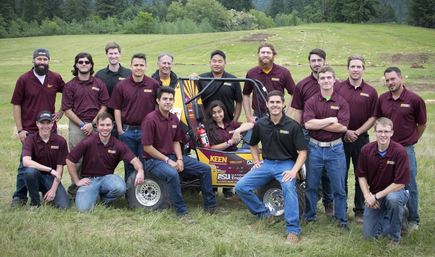 Photo of a large group of people with a race car in a field.
