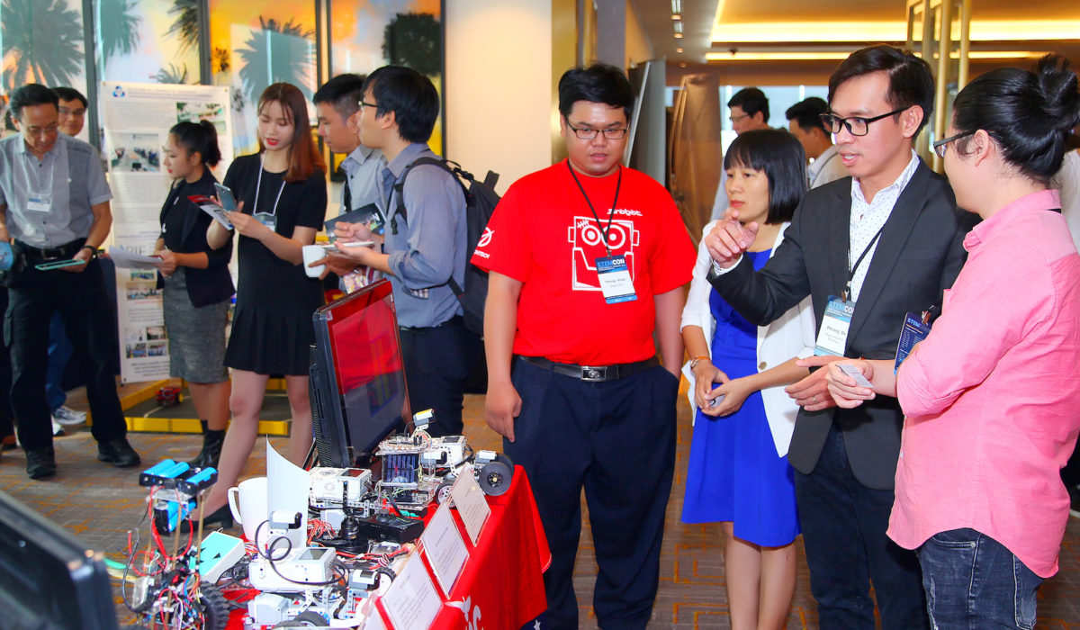 Participants visit student-created robots at the Saigon Tech booth in the STEM Innovation Showcase Exhibition at STEMCON.
