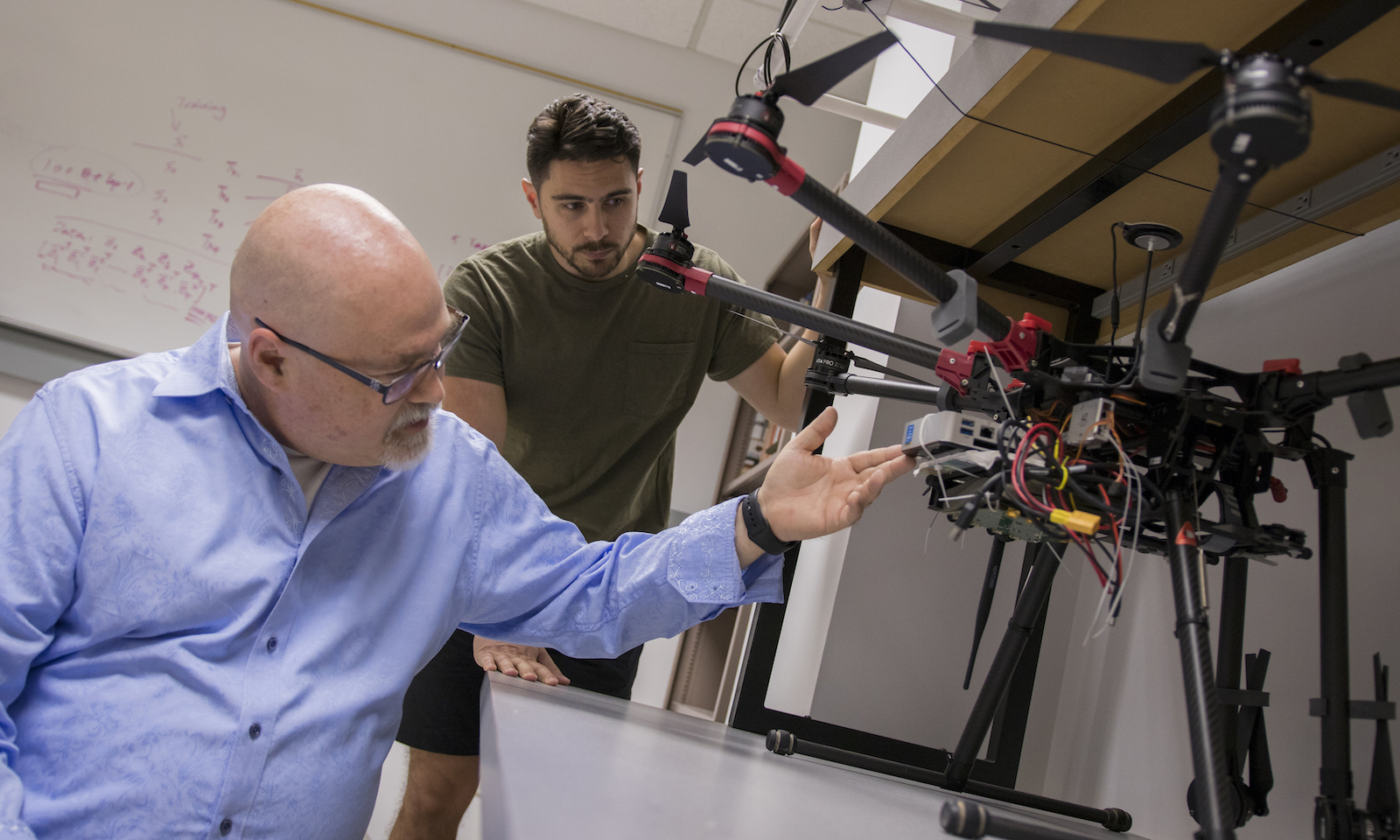 Professor and student looking at a drone