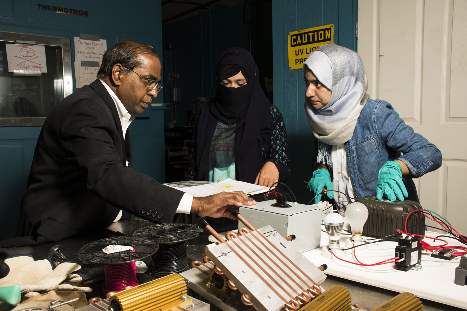 Photo of professor working with two female students
