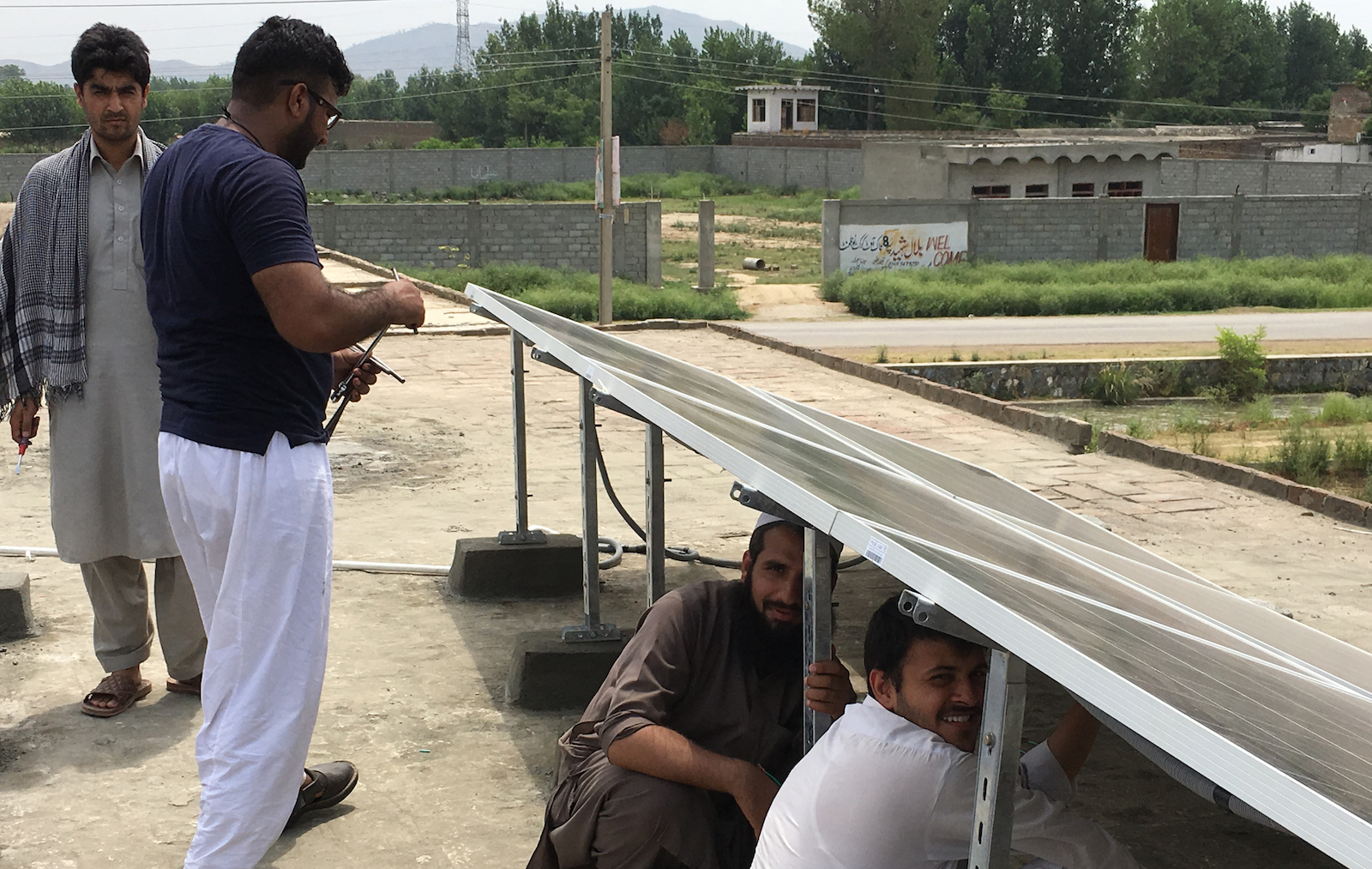 Four men working outdoors on solar panels in Pakistan