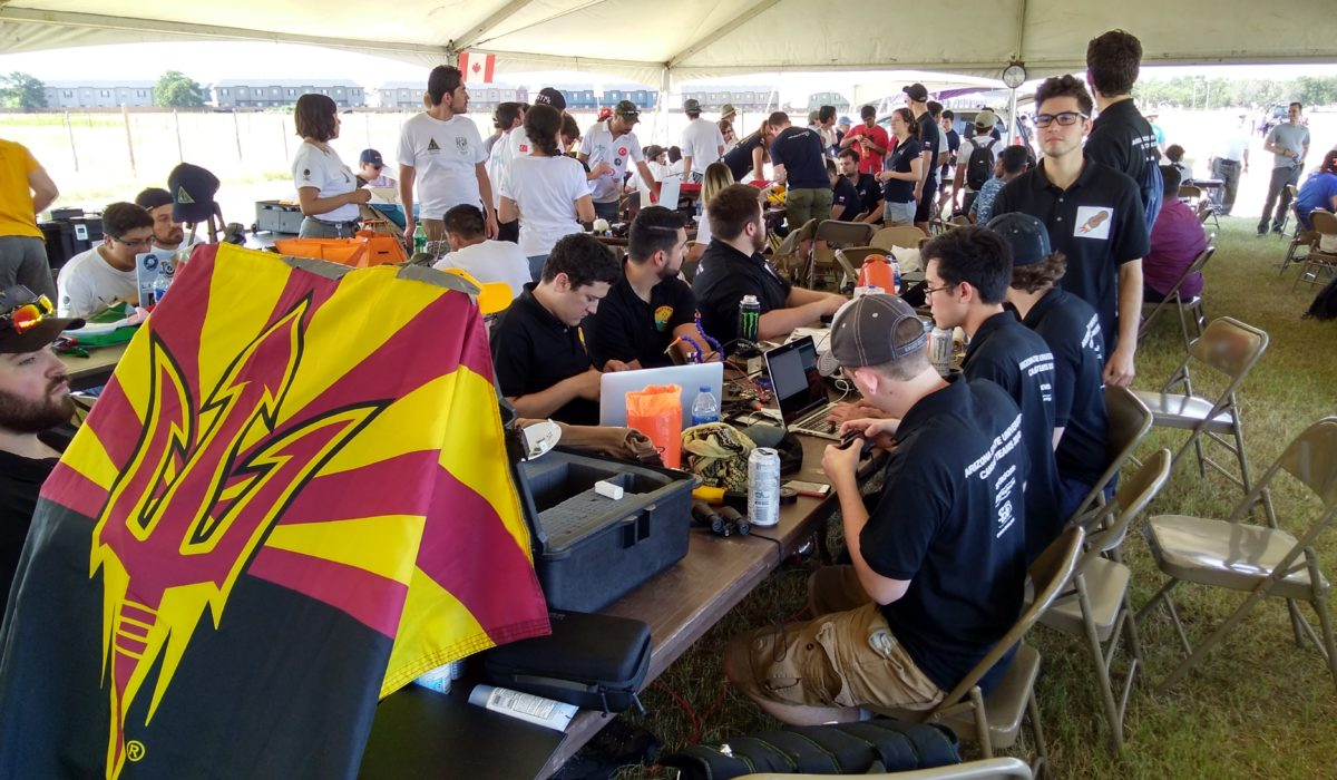 students sitting at a table under a large tent