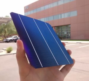 hand holding a solar cell outdoors