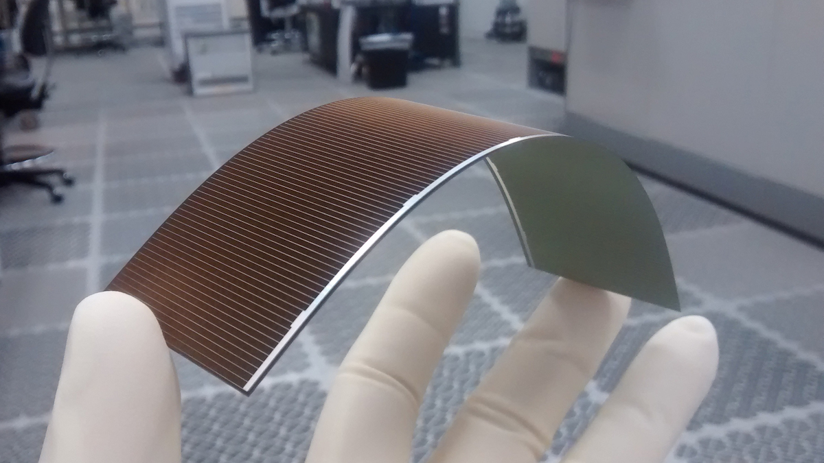 A thin solar cell being flexed in a hand