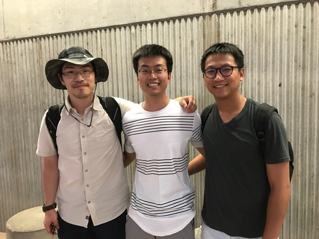 three students standing in a row