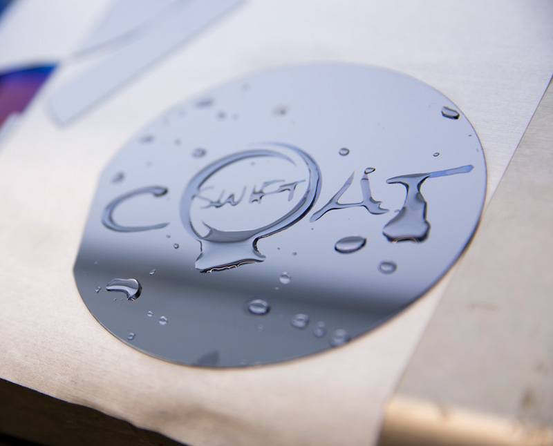 A reflective disk with the Swift Coat logo